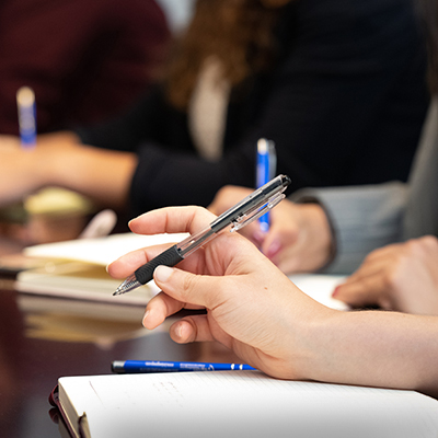 Experienced immigration attorney holding a pen in a meeting
