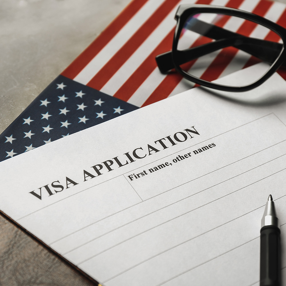 Photo of a visa application on top of a US flag